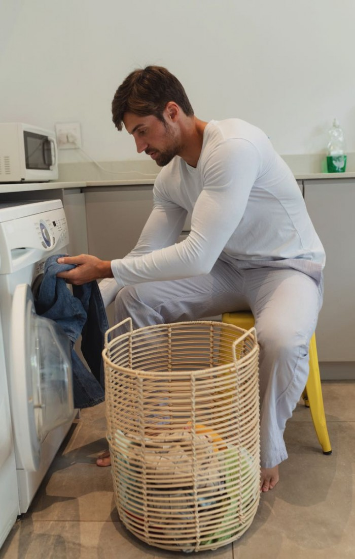 side-view-of-young-caucasian-man-putting-clothes-i-A3JFQ8T.jpg